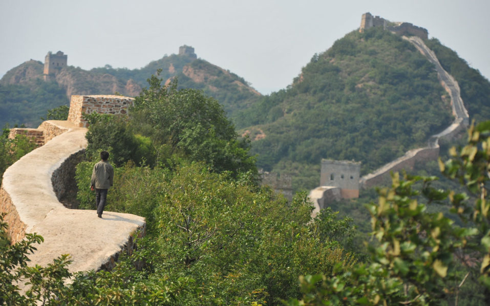 "This picture taken on September 21, 2016 shows a villager walking on a paved-over section of the Great Wall of China at Suizhong, in China's northeast Liaoning province. Chinese social media users were in an uproar on September 23 over restoration of a 700-year-old section of the Great Wall that has been covered in concrete, turning it into a smooth, flat-topped path. Known as one of the most beautiful portions of the ""wild"", unrestored wall, the eight-kilometre (five-mile) Xiaohekou stretch in northeast Liaoning province was built in 1381 during the Ming Dynasty. / AFP PHOTO / STR / China OUT"