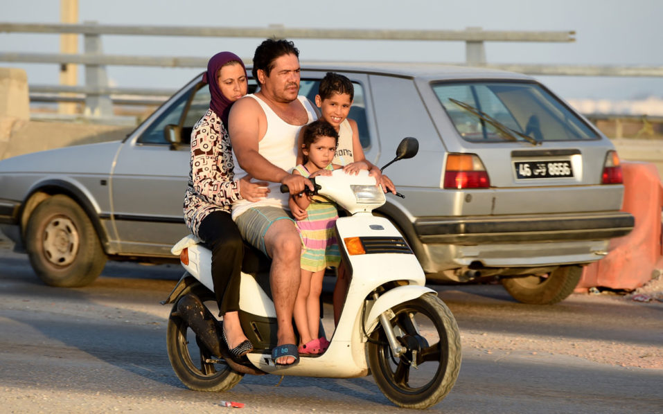 A Tunisian family returns from the beach on the motorway from the port city of La Goulette to Tunis on the outskirts of the Tunisian capital on July 12, 2016.  Run-down roads, reckless driving and poor vehicle maintenance are all being blamed for a spike in deadly traffic accidents in Tunisia that has safety experts worried. Road traffic deaths rose by nine percent in the first five months of this year compared with 2015, sparking calls for tougher measures to crack down on widespread traffic offences. / AFP PHOTO / FETHI BELAID / TO GO WITH AFP STORY BY KAOUTHER LARBI