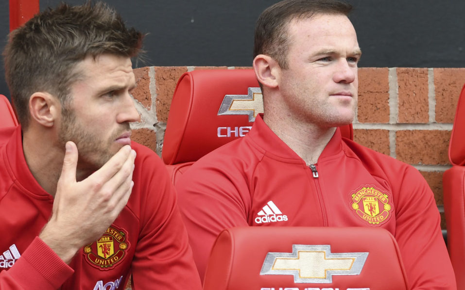 Manchester United's English striker Wayne Rooney (R) sits on the substitutes bench with Manchester United's English midfielder Michael Carrick (L) during the English Premier League football match between Manchester United and Leicester City at Old Trafford in Manchester, north west England, on September 24, 2016. / AFP PHOTO / ANTHONY DEVLIN /