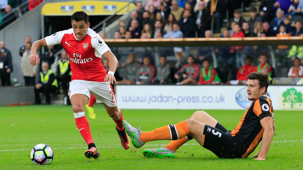 Arsenal's Chilean striker Alexis Sanchez (L) rounds Hull City's English defender Harry Maguire to score during the English Premier League football match between Hull City and Arsenal at the KCOM Stadium in Kingston upon Hull, north east England on September 17, 2016. PHOTO: Andy Buchanan / AFP