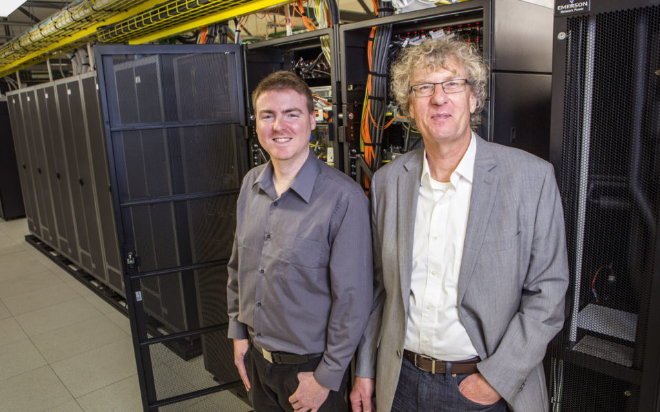 This handout photo taken on September 6, 2016 and released on September 26, 2016 shows University of Canterbury alumni composer Jason Long (L) and professor Jack Copeland (R) in the UNIVER Blue Gene computer area. New Zealand researchers said on September 26 they have restored the first recording of computer-generated music, created in 1951 on a gigantic contraption built by British genius Alan Turing. / AFP PHOTO / UNIVERSITY OF CANTERBURY / STR /