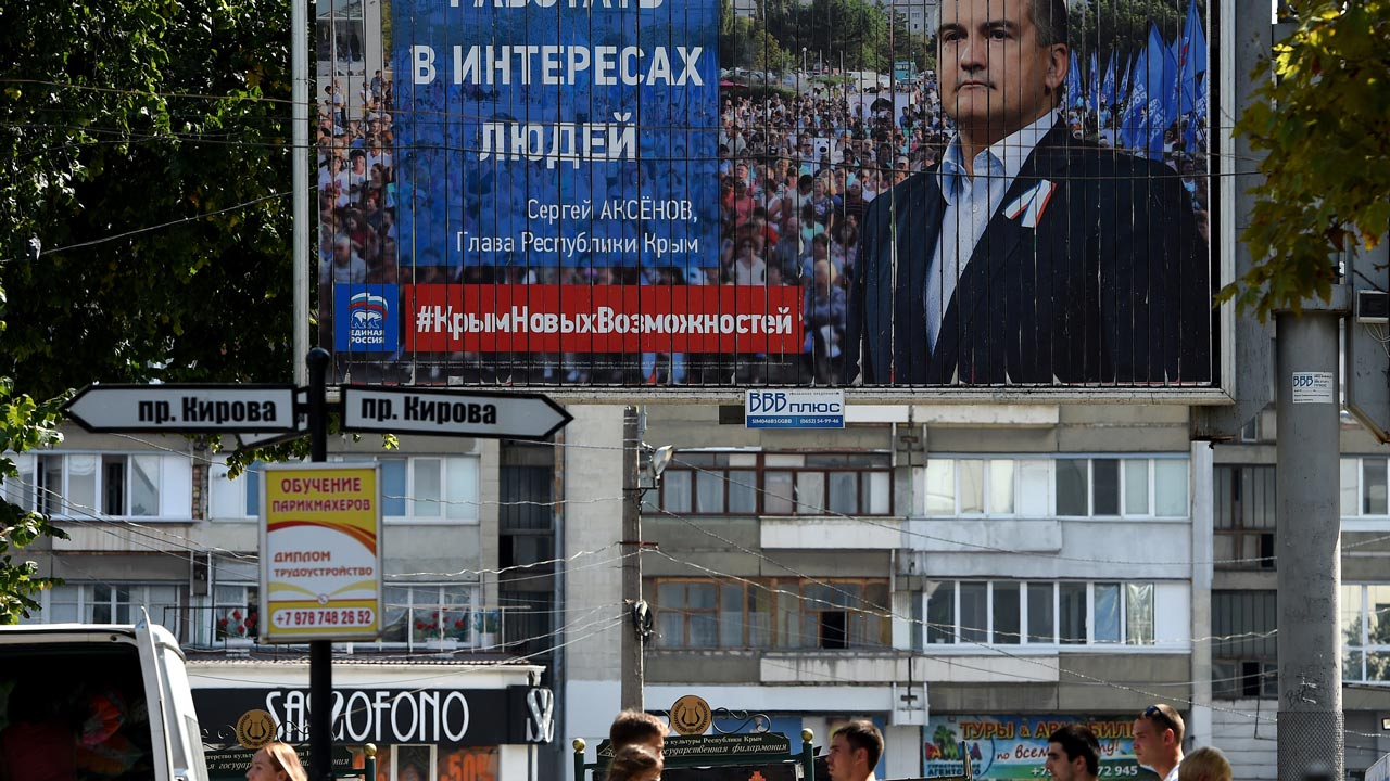 A picture taken on September 10, 2016 in the main Crimean city of Simferopol shows people walking next to an election billboard for the United Russia party with a portrait of Crimean leader Sergei Aksyonov. Two-and-a-half years after Moscow annexed the strategic peninsula from Ukraine, residents are gearing up to vote Sunday in their first polls to elect deputies to Russia's national parliament. The ballot in Crimea -- not recognised by Kiev or the international community -- looks set to bind the region still closer to Moscow as the new pro-Kremlin elite cements its grip and opposition is silenced. PHOTO: VASILY MAXIMOV / AFP