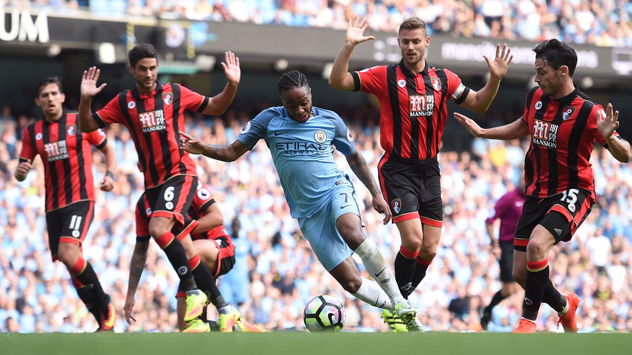 Manchester City's English midfielder Raheem Sterling (C) wriggles past Bournemouth's South African-born English midfielder Andrew Surman (2L) and Bournemouth's English defender Simon Francis (2R) during the English Premier League football match between Manchester City and Bournemouth at the Etihad Stadium in Manchester, north west England, on September 17, 2016. PAUL ELLIS / AFP