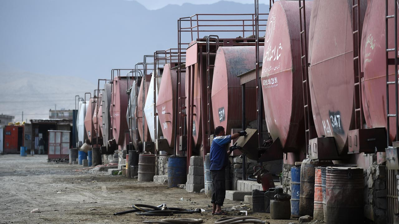 In this photograph taken on August 29, 2016, Afghan workers fill fuel containers from fuel tankers at a oil depot on the outskirts of Kabul. Tax-exempt military fuel imported into Afghanistan is being sold on the open market, industry officials and a new anti-corruption report reveal, causing the government huge revenue losses as Kabul struggles to wean itself off foreign aid. PHOTO: WAKIL KOHSAR / AFP