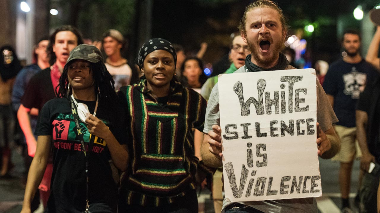 CHARLOTTE, NC - SEPTEMBER 22: Demonstrators march together in protest on September 22, 2016 in Charlotte, NC. Protests began on Tuesday night following the fatal shooting of 43-year-old Keith Lamont Scott at an apartment complex near UNC Charlotte. A state of emergency was declared overnight in Charlotte and a midnight curfew was imposed by mayor Jennifer Roberts, to be lifted at 6 a.m. Sean Rayford/Getty Images/AFP Sean Rayford / GETTY IMAGES NORTH AMERICA / AFP