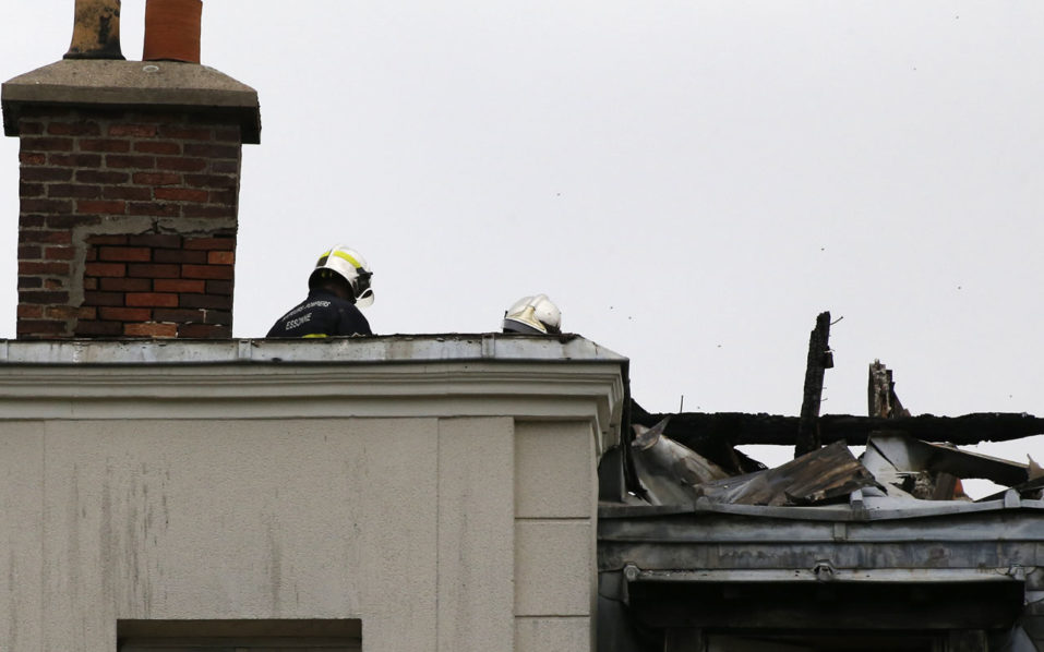 Firefighters assess damages on the roof of a future migrant center after an alleged arson attack that occured overnight on September 6, 2016 in Forges-les-Bains, some 50 kilometers southwest of Paris.   The incident occured the day Paris mayor Anne Hidalgo unveiled plans to take hundreds of people off the streets as France struggles to accommodate migrants. The place was set to accomodate from October some ninety asylum seekers from Sudan and Afghanistan. The General Director of Emmaus Solidarity, the association in charge of the center, confirmed it will indeed open. / AFP PHOTO / MATTHIEU ALEXANDRE