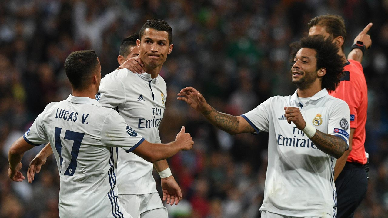 Real Madrid's Portuguese forward Cristiano Ronaldo (C) is congratulated by Real Madrid's Brazilian defender Marcelo after scoring during the UEFA Champions League football match Real Madrid CF vs Sporting CP at the Santiago Bernabeu stadium in Madrid on September 14, 2016. Real Madrid won 2-1. GERARD JULIEN / AFP