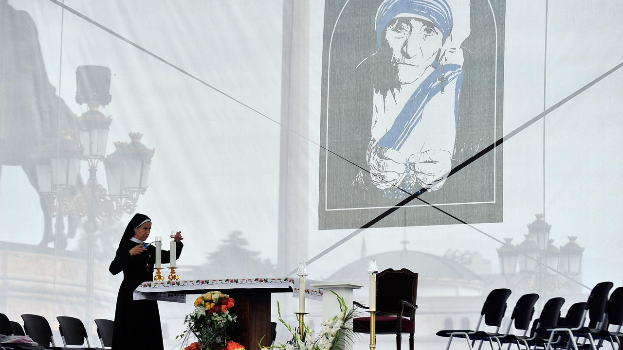 A nun lights a candle as she attends celebrations in the main square in Skopje, on September 11, 2016, at the conclusion of a special day of thanksgiving for the canonization of Mother Teresa. Pope Francis on September 4 proclaimed Mother Teresa a saint, hailing her work with the destitute of Kolkata as a beacon for mankind and testimony of God's compassion for the poor. PHOTO: Robert ATANASOVSKI / AFP
