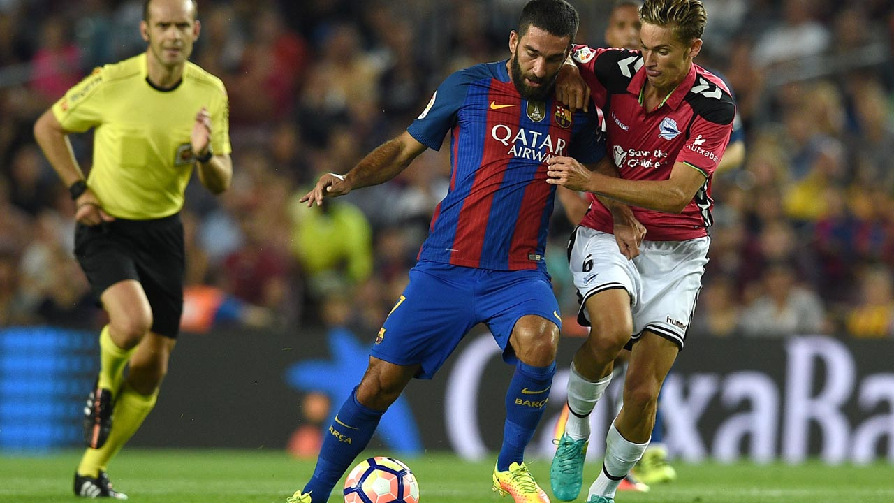 Barcelona's Turkish forward Arda Turan (L) vies with Alaves' midfielder Marcos Llorente during the Spanish league football match FC Barcelona vs Deportivo Alaves at the Camp Nou stadium in Barcelona on September 10, 2016. PHOTO: LLUIS GENE / AFP