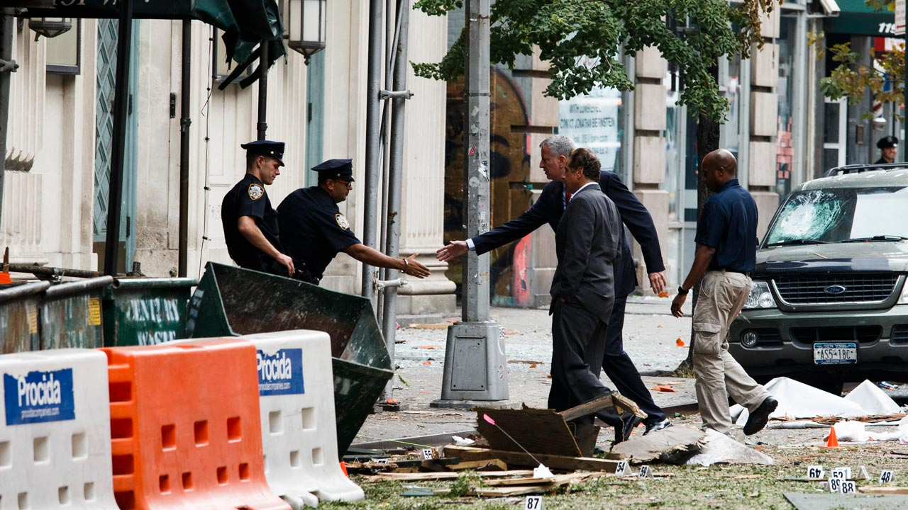 New York Mayor Bill de Blasio (3-R) and New York Governor Andrew Cuomo (2-R) greet officers at the site of an explosion that occurred in the Chelsea neighborhood of New York on September 18, 2016. The bomb that exploded in New York September 17 wounding 29 people was an act of terrorism that has no apparent international link, the state governor said Sunday. PHOTO: Justin LANE / POOL / AFP