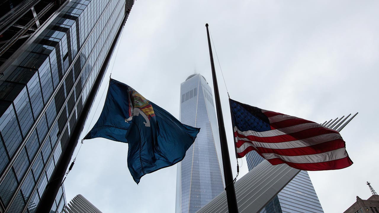 NEW YORK, NY - SEPTEMBER 11: A New York state flag and an American flag fly at half-mast in Lower Manhattan near One World Trade Center, September 11, 2016 in New York City. Throughout the country services are being held to remember the 2,977 people who were killed in New York, the Pentagon and in a field in rural Pennsylvania. Drew Angerer/Getty Images/AFP Drew Angerer / GETTY IMAGES NORTH AMERICA / AFP
