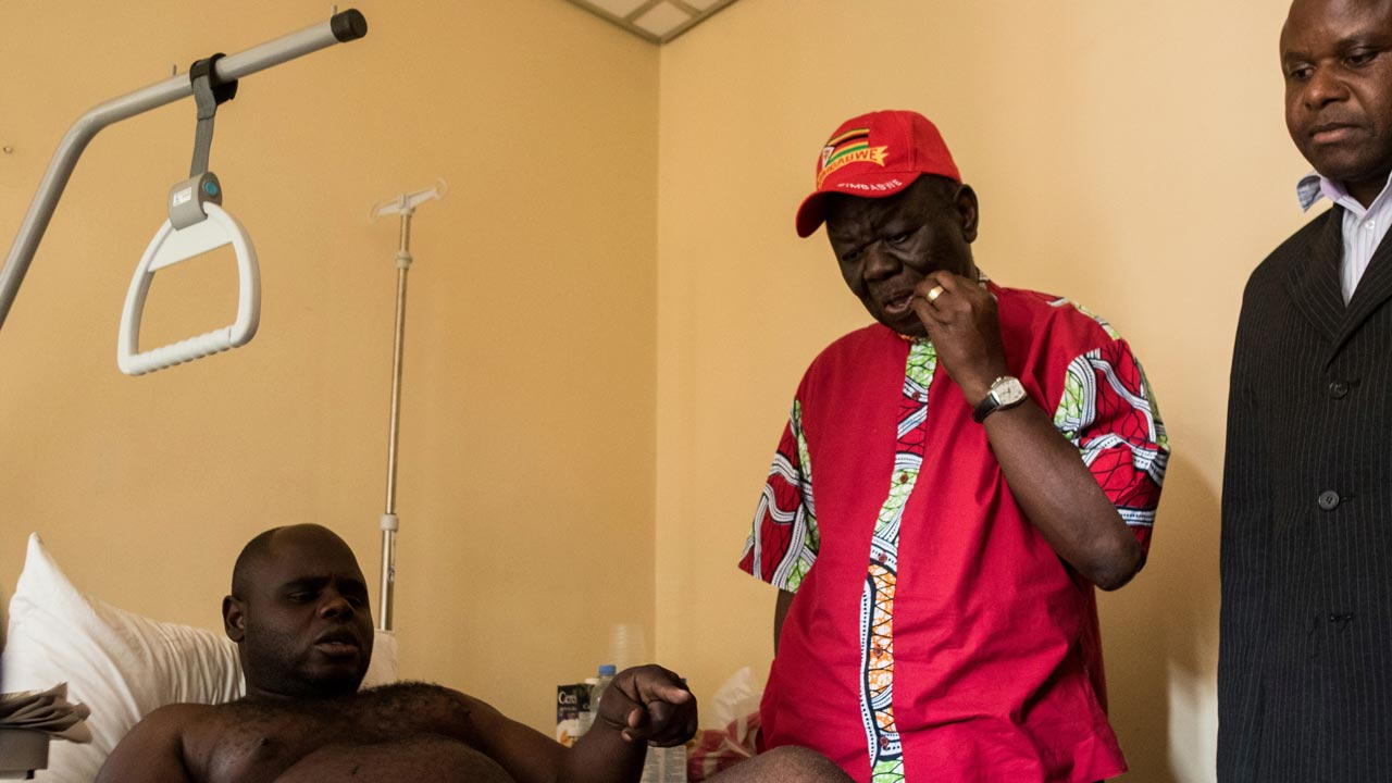 Zimbabwean protest theatre actor and activist Sylvanos Mudzvova explains to opposition leader Morgan Tsvangirai (C) of the Movement for Democratic Change (MDC) visits a local hospital in the capital Harare how he was allegedly tortured by unidentified men who abducted him from his Harare home and allegedly dumped him unconscious in a bush outside the capital, on September 15, 2016 in Harare. PHOTO: Jekesai Njikizana / AFP