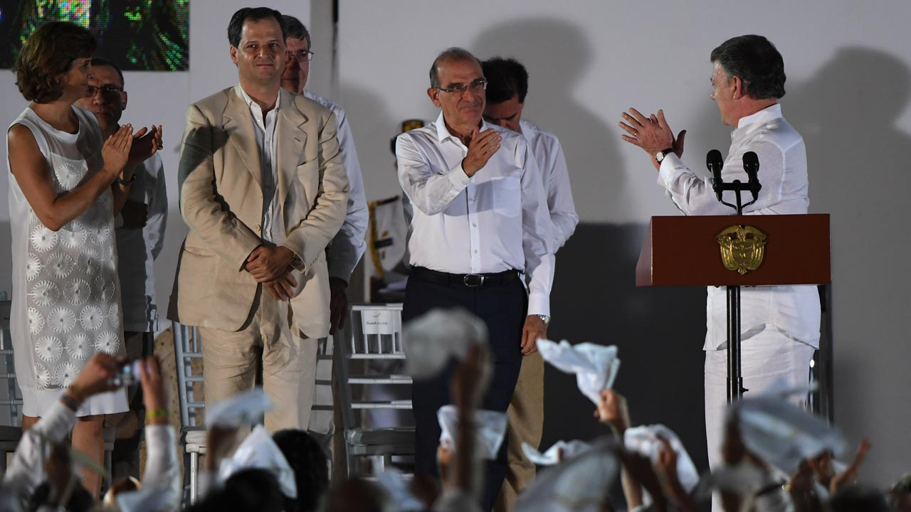 "Colombian President Juan Manuel Santos (R) looks at the head of the Colombian government's delegation of the peace talks with the FARC guerrillas, Humberto de la Calle (2-R) after delivering a speech after signing the historic peace agreement between the Colombian government and the Revolutionary Armed Forces of Colombia (FARC), in Cartagena, Colombia, on September 26, 2016 The Colombian government and the leftist FARC rebel force signed a historic peace accord to end a half-century conflict that has killed hundreds of thousands of people. Santos and ""Timochenko"" Jimenez, signed the deal at a ceremony in the Caribbean city of Cartagena, prompting loud cheers from the crowd which included numerous international dignitaries. Luis ACOSTA / AFP"
