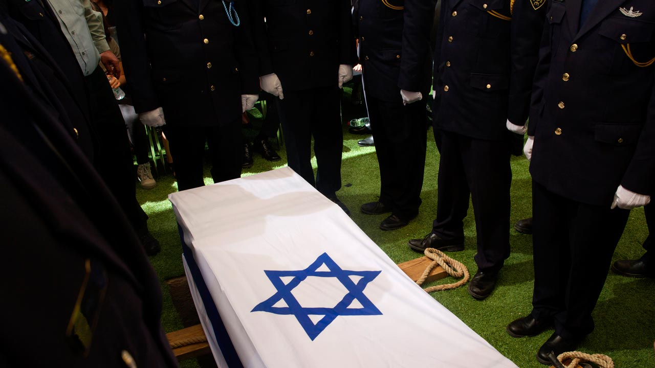 Members of the Knesset (parliamentary) guards stand beside the flag-draped coffin of former Israeli President Shimon Peres during the burial ceremony at the funeral at Mount Herzl National Cemetery in Jerusalem, on September 30, 2016. RONEN ZVULUN / POOL / AFP