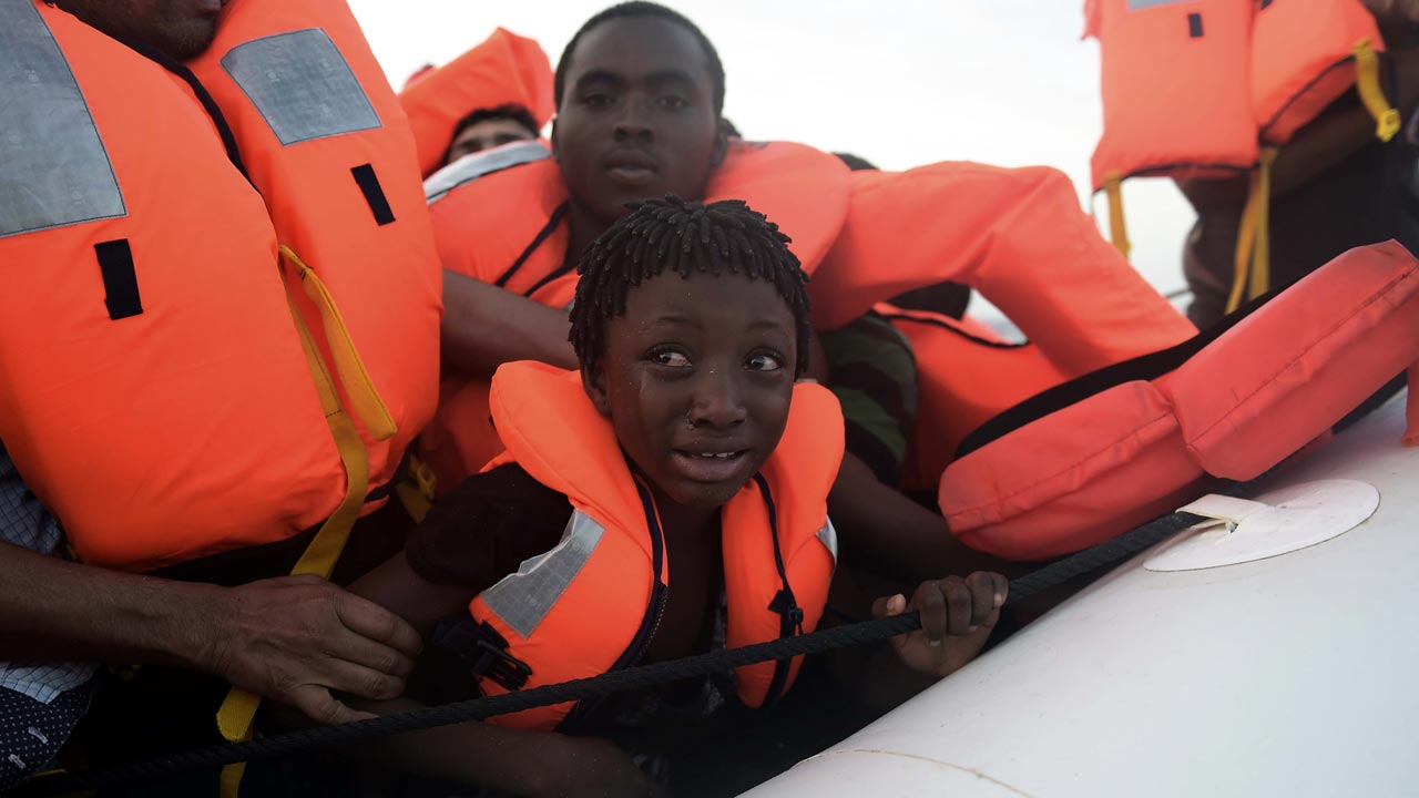 A child cries as migrants are being rescued by members of Proactiva Open Arms NGO in the Mediterranean Sea, some 12 nautical miles north of Libya, on October 4, 2016. At least 1,800 migrants were rescued off the Libyan coast, the Italian coastguard announced, adding that similar operations were underway around 15 other overloaded vessels. ARIS MESSINIS / AFP