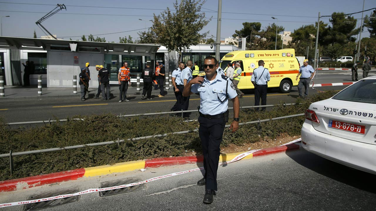 sraeli security forces and policemen gather at the site of a shooting attack near Israeli police headquarters, close to the line dividing mainly Palestinian east Jerusalem from the mostly Jewish western sector of the city, on October 9, 2016. A Palestinian opened fire from a car in Jerusalem, wounding four people out of which two have died, police shot him dead, authorities said. AHMAD GHARABLI / AFP