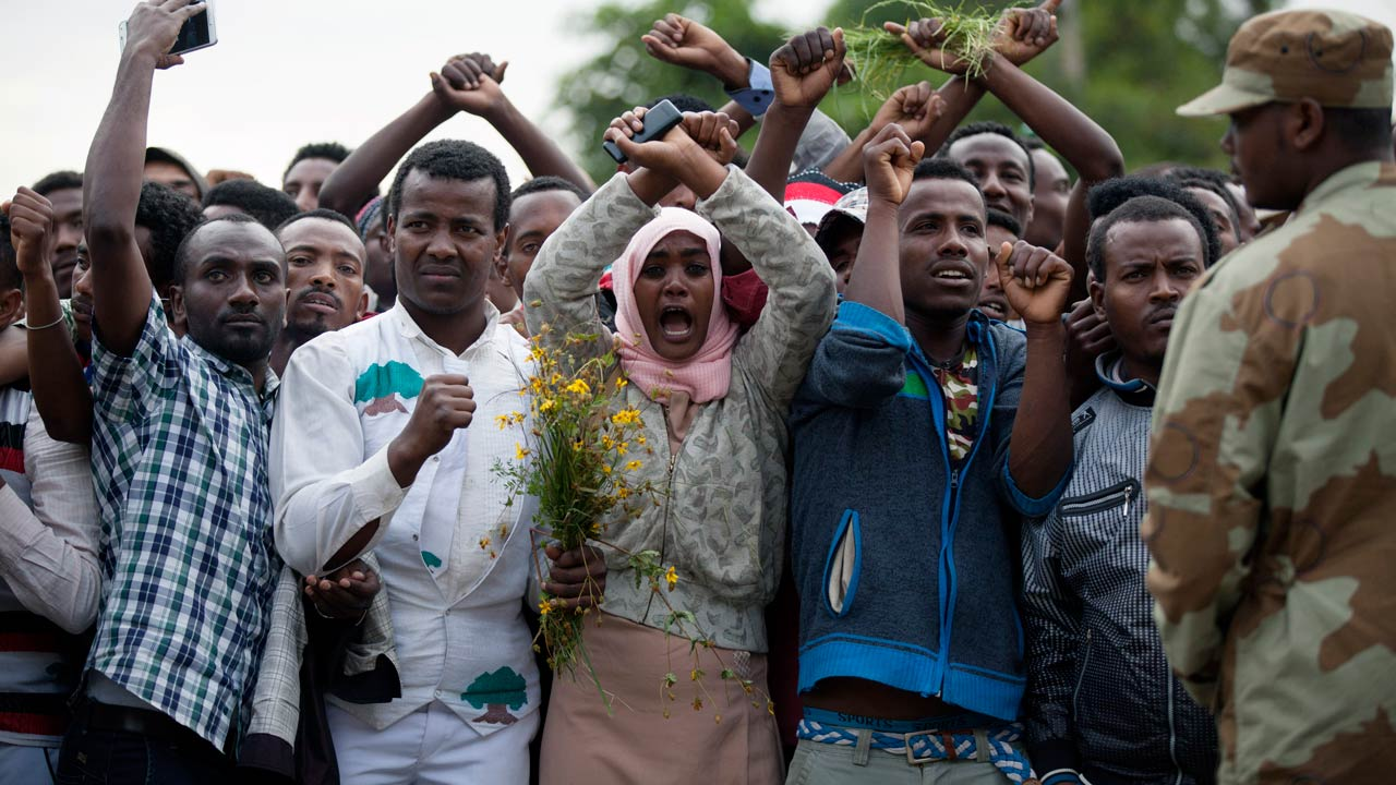 "(FILES) This file photo taken on October 2, 2016 shows residents of Bishoftu crossing their wrists above their heads as a symbol for the Oromo anti-government protesting movement during the Oromo new year holiday Irreechaa in Bishoftu. Ethiopia declared a state of emergency on October 9, 2016 following months of violent anti-government protests, according to an official statement. ""The state of emergency was declared following a thorough discussion by the Council of Ministers on the loss of lives and property damages occurring in the country,"" Prime Minister Hailemariam Desalegn said. Zacharias ABUBEKER / AFP"