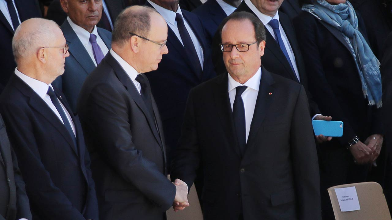 French President Francois Hollande (R) shakes hands with Prince Albert of Monaco (C) during a national tribute on October 15, 2016 in Nice, southeastern France in memory of the victims of the July 14 terror attack in which a truck ploughed into crowds celebrating Bastille Day, killing 86 people and injuring more than 400. In the attack, a 31-year-old Tunisian extremist rammed a 19-ton truck through a crowd of more than 30,000 Bastille Day revellers on the seafront Promenade des Anglais before police shot him dead. The Islamic State (IS) group said the driver of the truck, Mohamed Lahouaiej Bouhlel, was one of its followers. VALERY HACHE / AFP