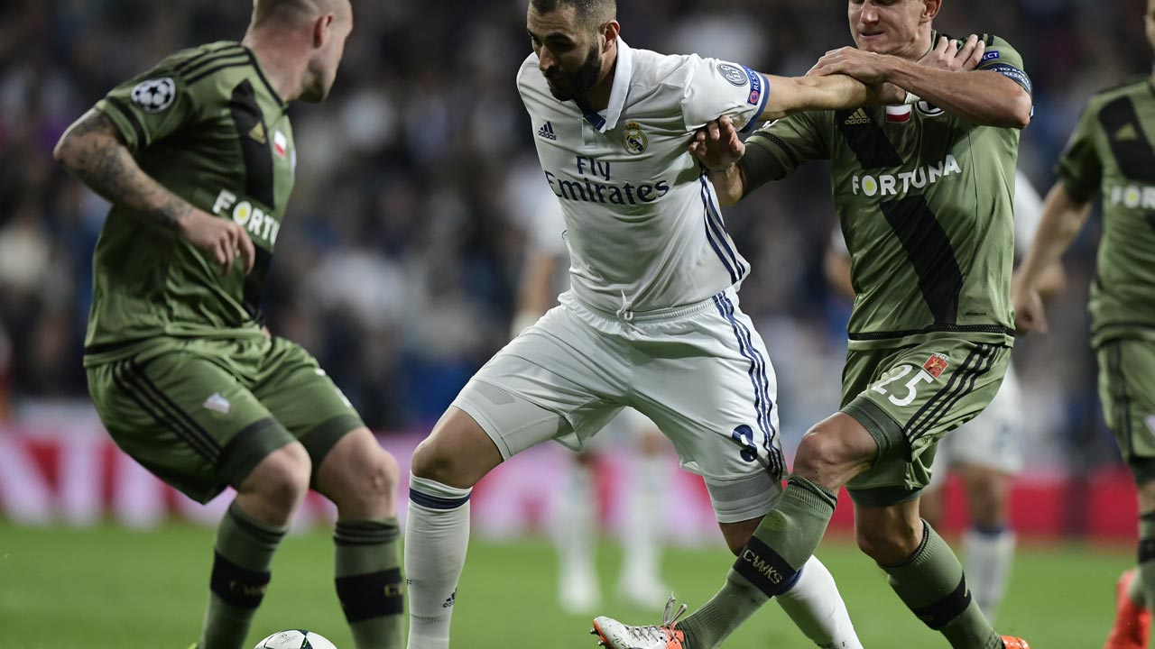 Real Madrid's French forward Karim Benzema (C) vies with Legia Warszawa's defender Jakub Rzezniczak during the UEFA Champions League football match Real Madrid CF vs Legia Legia Warszawa at the Santiago Bernabeu stadium in Madrid on October 18, 2016. JAVIER SORIANO / AFP