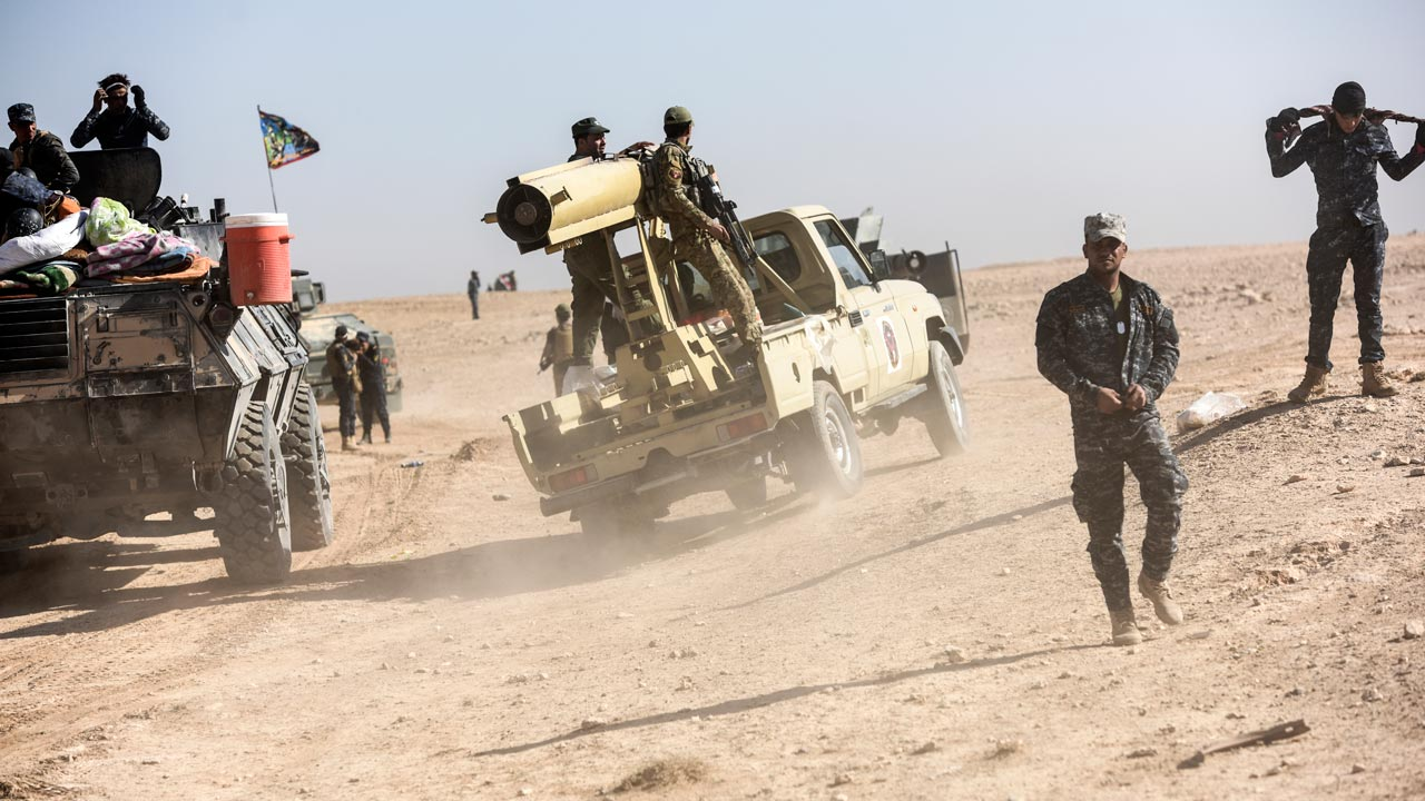 Members of Iraqi pro-government forces drive towards the frontline on October 21, 2016 near the village of Tall al-Tibah, some 30 kilometres south of Mosul, during an operation to retake the main hub city from the Islamic State (IS) group jihadists. The operation is Iraq's biggest in years and aims to wrest back Mosul, the country's second city and the last major IS stronghold in Iraq. BULENT KILIC / AFP