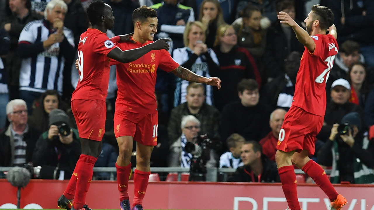 Liverpool's Brazilian midfielder Philippe Coutinho (C) celebrates scoring their second goal with Liverpool's Senegalese midfielder Sadio Mane (L) and Liverpool's English midfielder Adam Lallana (R) during the English Premier League football match between Liverpool and West Bromwich Albion at Anfield in Liverpool, north west England on October 22, 2016. PAUL ELLIS / AFP