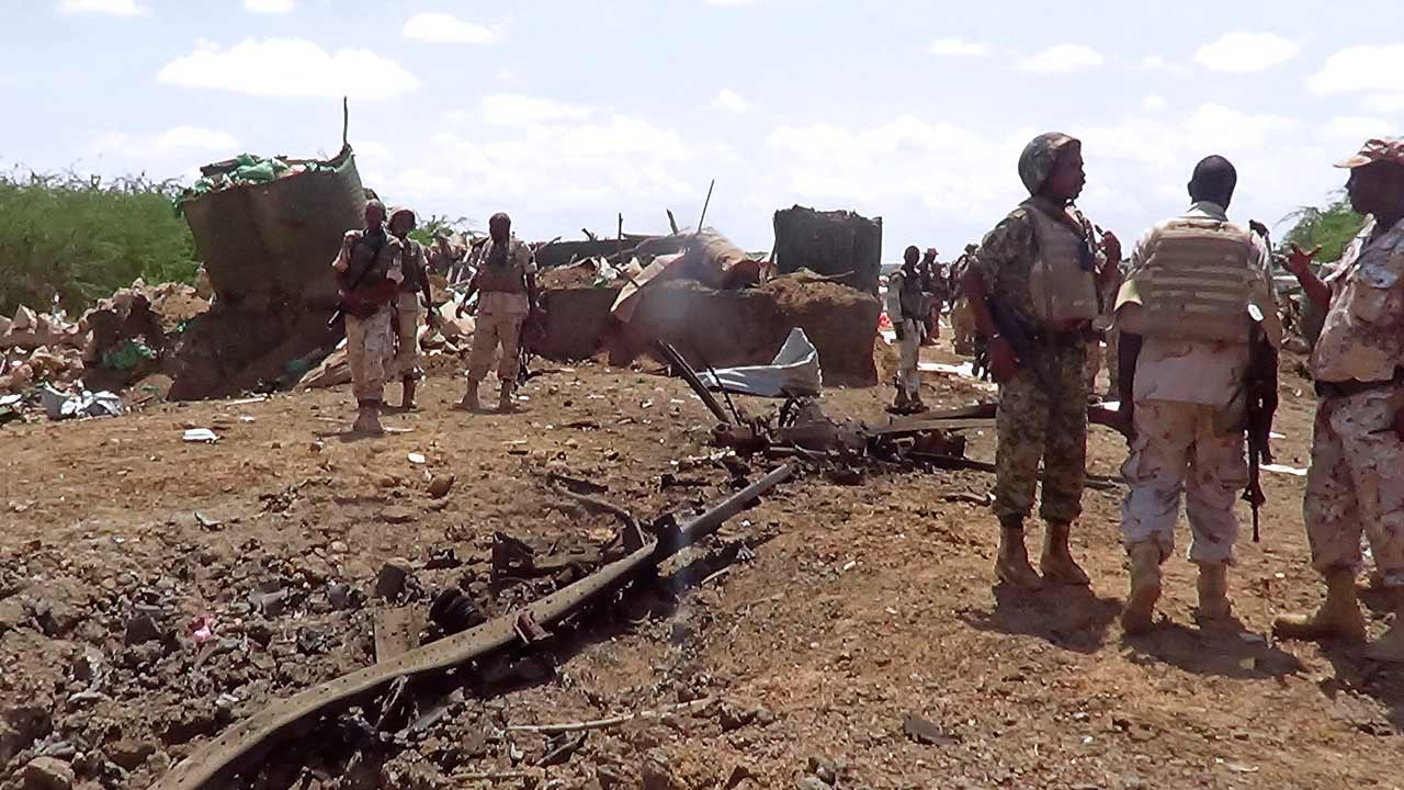 African Union soldiers from Djibouti stand at the site of a car bomb attack at an African Union army base in central Somalia on October 25, 2016. A Shabaab suicide bomber rammed a vehicle loaded with explosives into an African Union military base in central Somalia today, a security official said. The explosion was followed by heavy gunfire at the Djiboutian base in the city of Beledweyne. PHOTO: STR / AFP