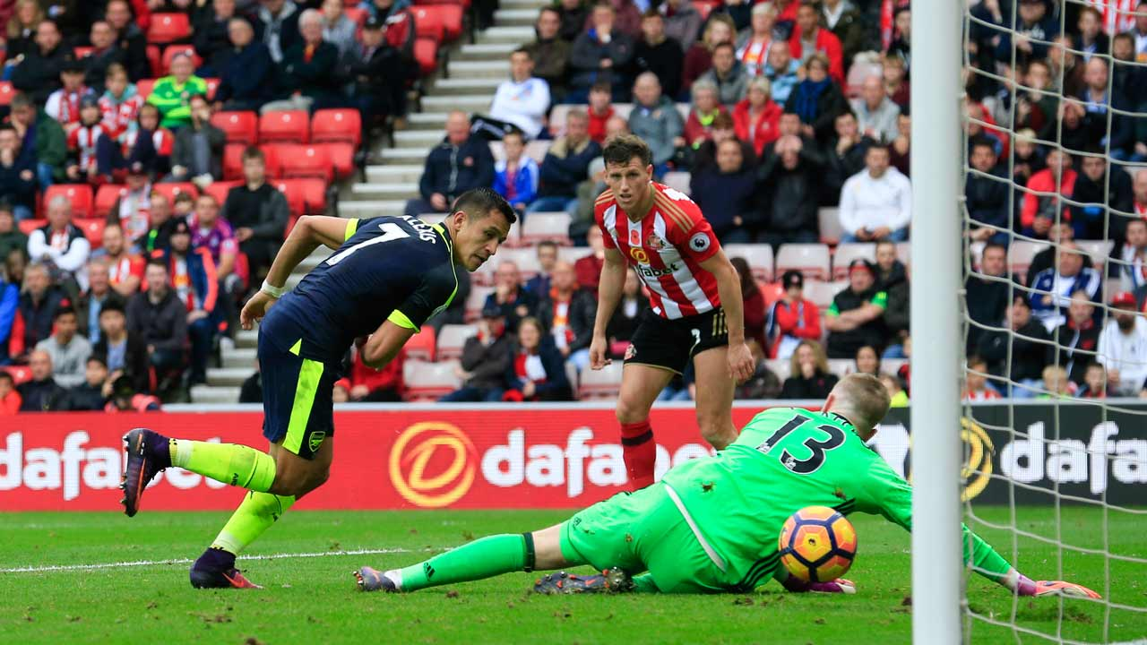 Arsenal's Chilean striker Alexis Sanchez (L) scores their fourth goal during the English Premier League football match between Sunderland and Arsenal at the Stadium of Light in Sunderland, northeast England on October 29, 2016. PHOTO: Lindsey PARNABY / AFP