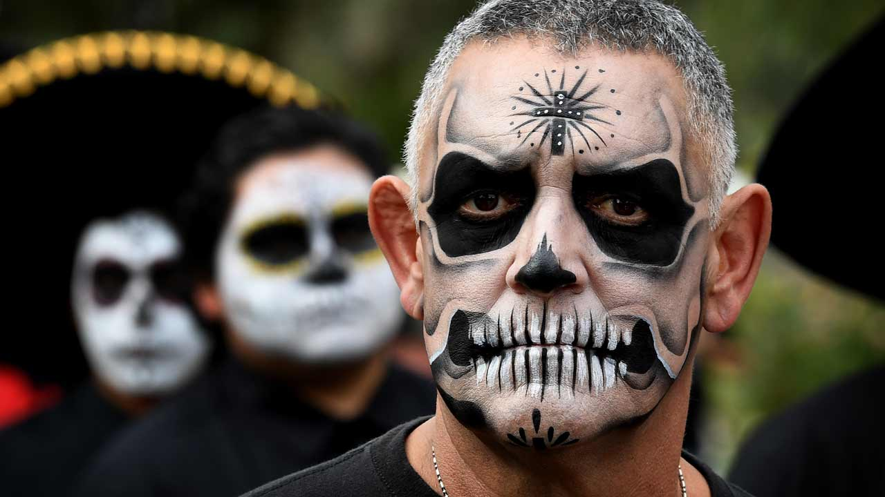 People in costume parade during the annual Dia de los Muertos (Day of the Dead) festival at the Hollywood Forever cemetery in Hollywood, California on October 29, 2016. Dia de los Muertos is a festival to remember friends and family members who have died and is celebrated throughout Mexico and by people of Mexican heritage living in the United States. PHOTO: Mark RALSTON / AFP