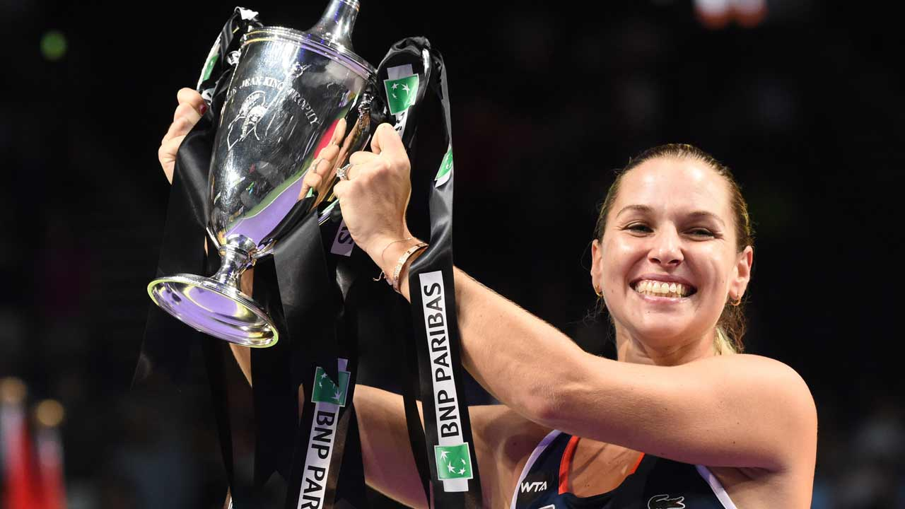 Dominika Cibulkova of Slovakia lifts the trophy after victory against Germany's Angelique Kerber at the end of their women's singles final at the WTA Finals tennis tournament in Singapore on October 30, 2016. ROSLAN RAHMAN / AFP