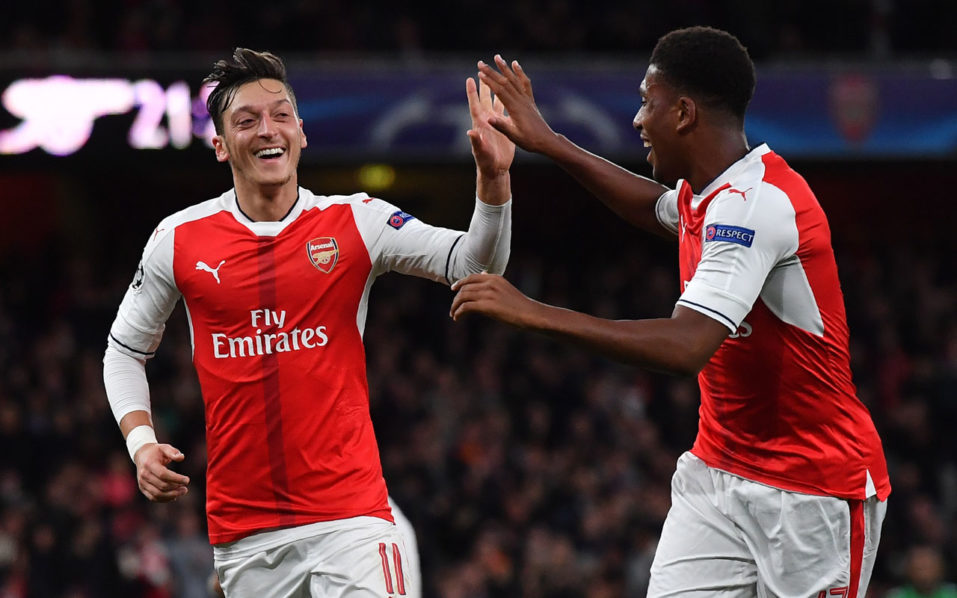 Arsenal's German midfielder Mesut Ozil (O) celebrates scoring his team's sixth goal with Arsenal's Nigerian striker Alex Iwobi during the UEFA Champions League Group A football match between Arsenal and Ludogorets Razgrad at The Emirates Stadium in London on October 19, 2016. / AFP PHOTO / BEN STANSALL