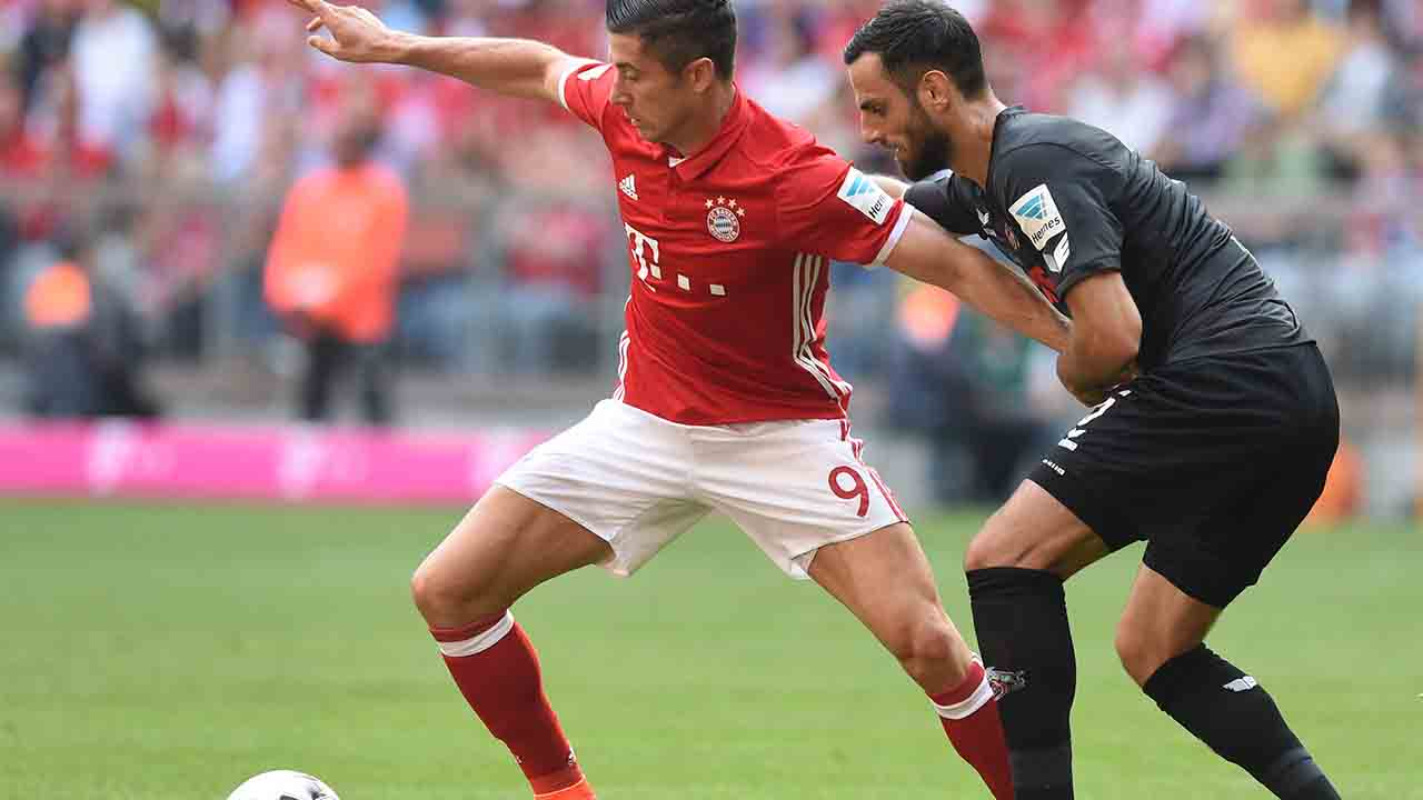 Bayern Munich's Polish striker Robert Lewandowski (L) and Cologne's Albanian defender Mergim Mavraj (R) vie for the ball during the German first division Bundesliga football match between FC Bayern Munich and 1 FC Cologne in Munich, southern Germany, on October 1, 2016. / AFP PHOTO / CHRISTOF STACHE / RESTRICTIONS: DURING MATCH TIME: DFL RULES TO LIMIT THE ONLINE USAGE TO 15 PICTURES PER MATCH AND FORBID IMAGE SEQUENCES TO SIMULATE VIDEO. == RESTRICTED TO EDITORIAL USE == FOR FURTHER QUERIES PLEASE CONTACT DFL DIRECTLY AT + 49 69 650050