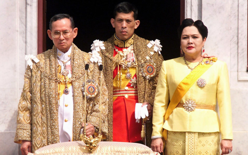 (L-R) Thai King Bhumibol Adulyadej, Crown Prince Maha Vajiralongkorn and Queen Sirikit appearing at a balcony of Anantasamakom Throne Hall in Bangkok to mark the King's birthday. Thailand's King Bhumibol Adulyadej has died after a long illness, the palace announced on October 13, 2016, ending a remarkable seven-decade reign and leaving a divided people bereft of a towering and rare figure of unity. / AFP PHOTO / PORNCHAI KITTIWONGSAKUL