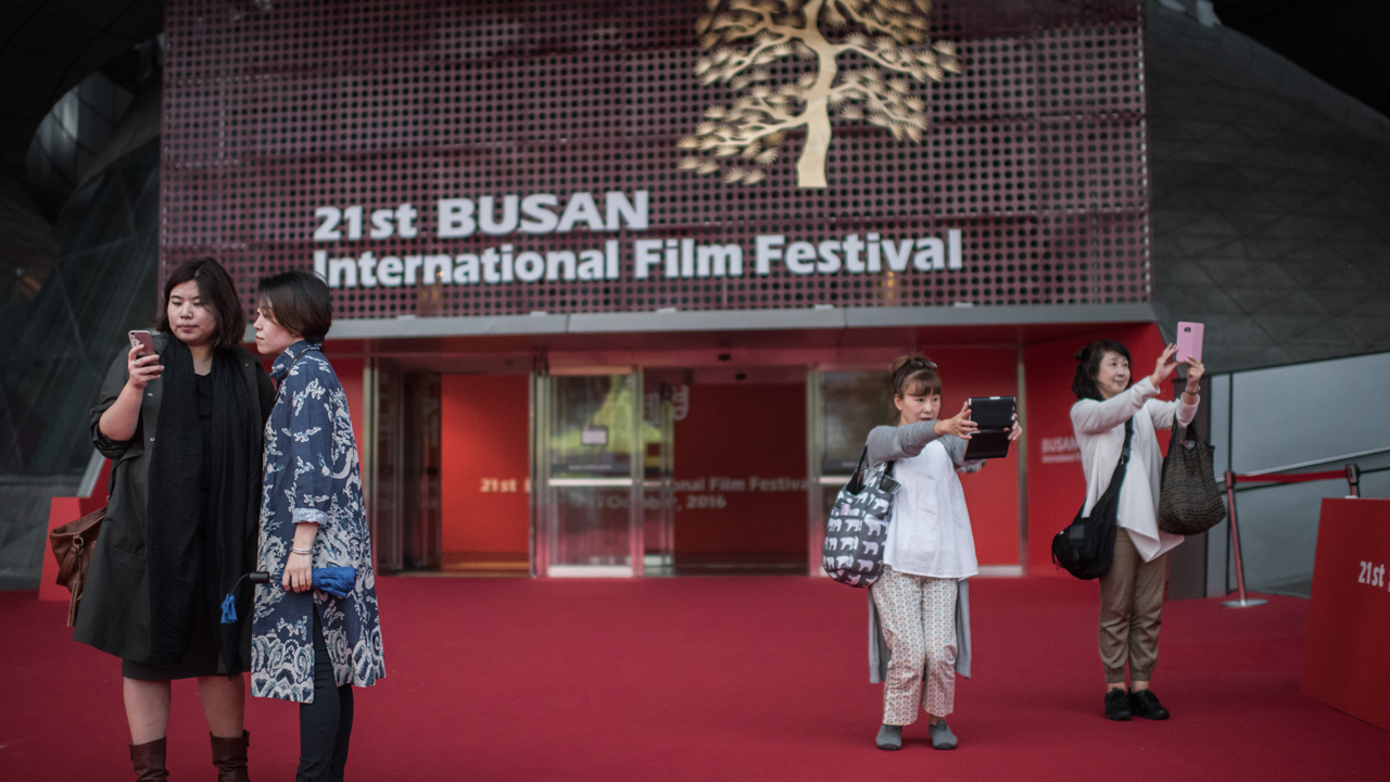 A photo taken on October 8, 2016 shows people posing before the entrance of the main venue of the Busan International Film Festival (BIFF), in Busan. This year's event is screening some 300 films from nearly 70 countries, including 66 features that will be receiving their world premieres. / AFP PHOTO / Ed Jones