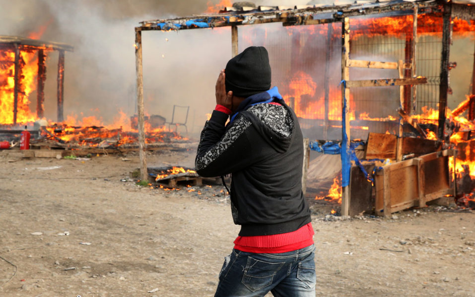 "A migrant walks past burning makeshift shelters during fires at the ""Jungle"" migrant camp in Calais, northern France, on October 26, 2016, during a massive operation to clear the squalid settlement where 6,000-8,000 people have been living in dire conditions.  Fresh fires broke out on October 26 in the ""Jungle"" migrant camp on the second day of operations to dismantle the squalid settlement in northern France. Smoke billowed over the sprawling camp near Calais for a second day amid fears that abandoned gas cylinders could explode.  / AFP PHOTO / François NASCIMBENI"