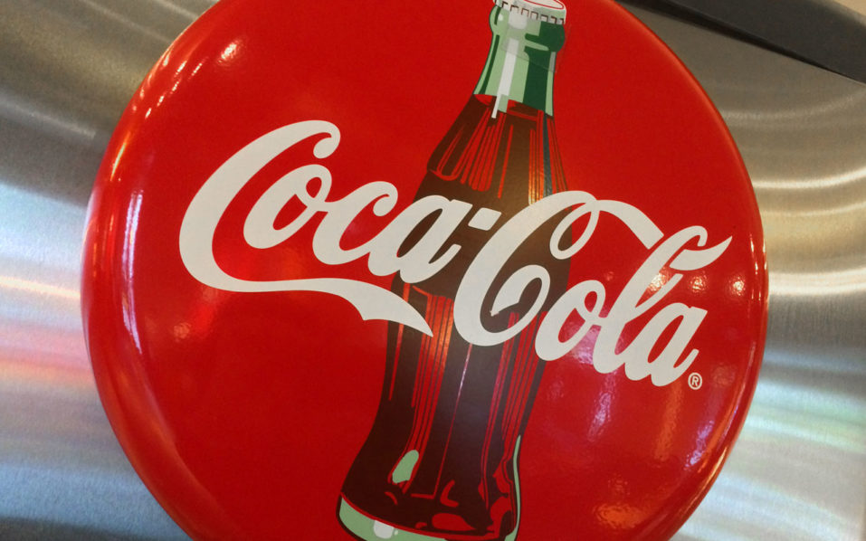 (FILES) This file photo taken on May 1, 2016 shows a Coca-Cola logo in a restaurant in Washington, DC. The slow global economy and the health-driven turn against sweet sodas dented Coca-Cola sales for the sixth straight quarter, delivering a 28 percent hit to net income, the company reported October 26, 2016. Coca-Cola said worldwide revenues fell in the quarter to September 30 by 7.0 percent from a year ago to $10.6 billion, with sharp declines in its Latin America and Europe-Africa-Middle East regions.  / AFP PHOTO / Karen BLEIER