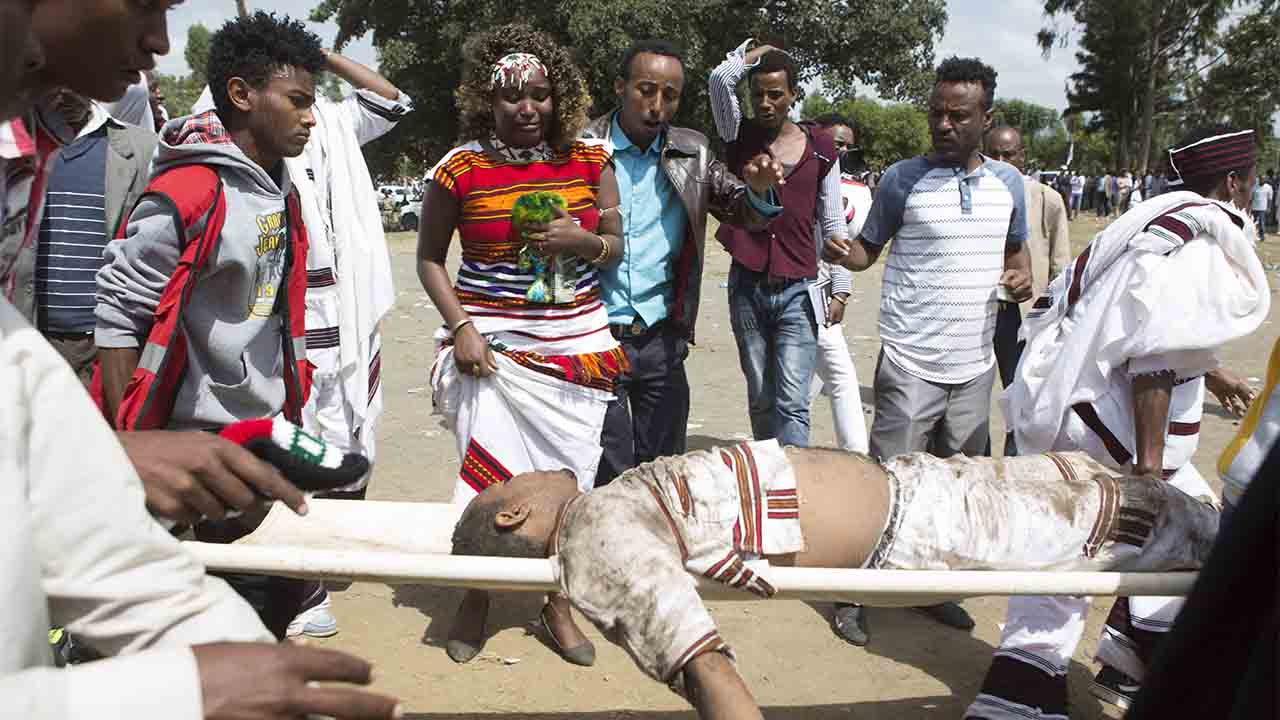 People look at a severely injured man carried for treatment after a deadly stampede in Bishoftu, on October 2, 2016.  Several people were killed in a stampede near the Ethiopian capital on October 2 after police fired tear gas at protesters during a religious festival, according to an AFP photographer at the scene. Several thousand people had gathered at a sacred lake to take part in the Irreecha ceremony, in which the Oromo community marks the end of the rainy season, where participants crossed their wrists above their heads, a gesture that has become a symbol of Oromo anti-government protests. The event quickly degenerated, with protesters throwing stones and bottles and security forces responding with baton charges and then tear gas grenades. / AFP PHOTO / Zacharias ABUBEKER