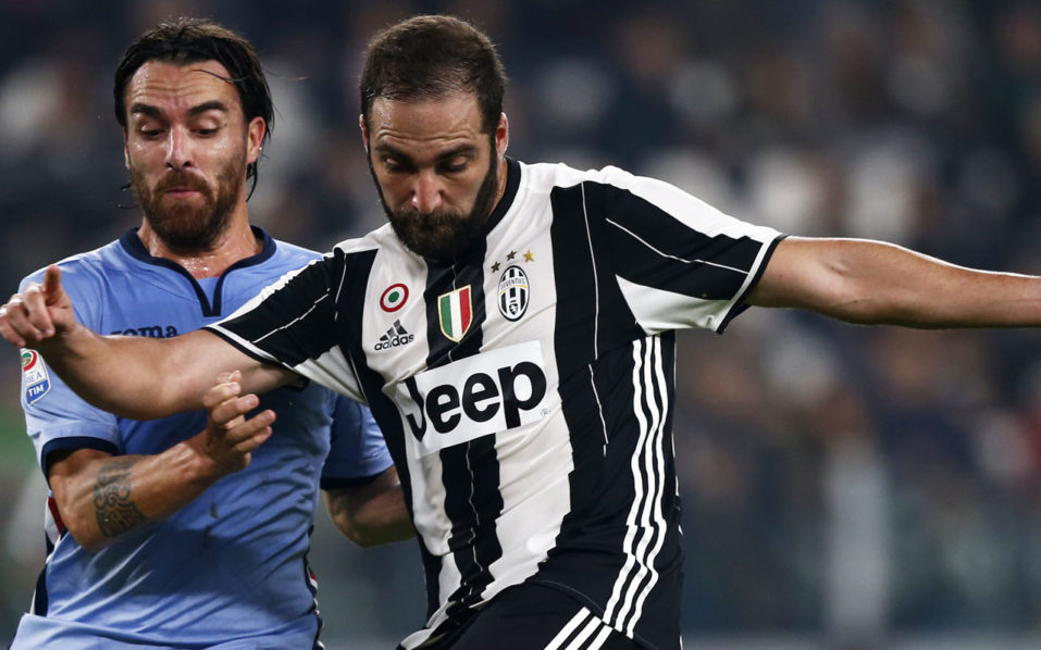 Sampdoria's midfielder Luca Cigarini (L) fights for the ball with Juventus' forward Gonzalo Higuain from Argentina during the Italian Serie A football match Juventus vs Sampdoria at the Juventus stadium in Turin on October 26, 2016. / AFP PHOTO / MARCO BERTORELLO /
