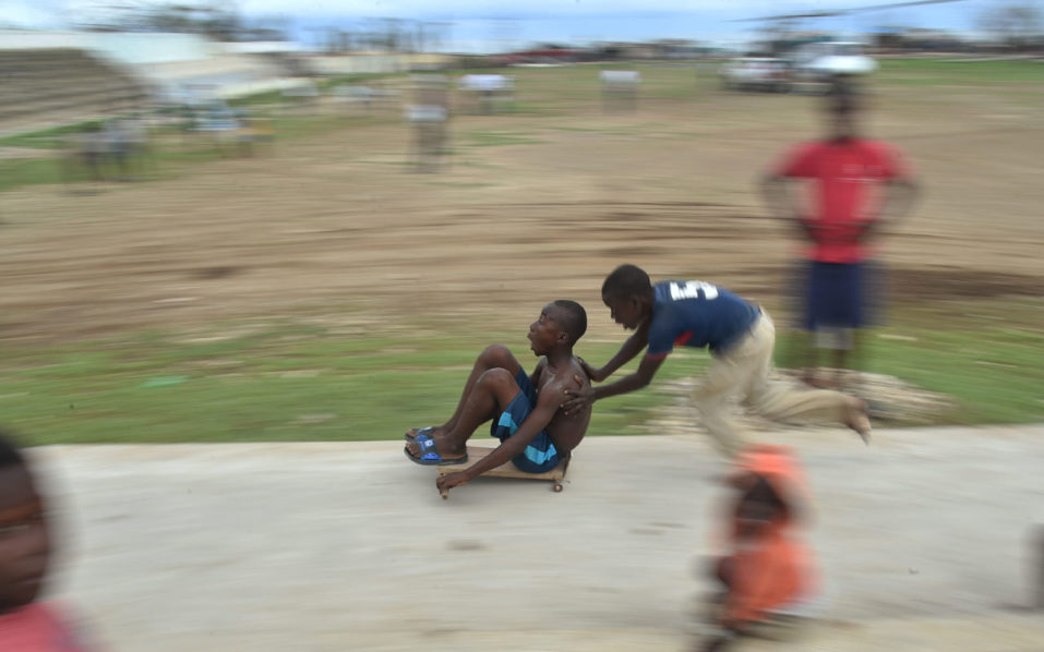 Children playing with cars made with wood and bearings in the neighborhood of Deye Distriyel in Jeremie, in the south west of Haiti, on October 23, 2016.   Following the devastation caused by Hurricane Matthew, nearly 1.5 million people, of a total population of 10.3 million, need emergency humanitarian assistance, according to a United Nations estimate. / AFP PHOTO / HECTOR RETAMAL