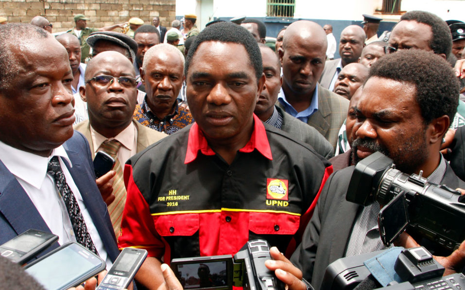(FILES) This file photo taken on March 2, 2016 shows opposition United Party for National Development president Hakainde Hichilema (C) talking to journalists before being dispersed with supporters athe Woodlands Police Station in Lusaka. Zambia's defeated election candidate Hakainde Hichilema on October 10, 2016 vowed to step up his battle to prove that the vote was rigged, after he was released on bail following his arrest. Hichilema, head of the United Party for National Development (UPND), dismissed Edgar Lungu's victory in August elections and said Zambia was enduring an unprecedented bout of political repression. / AFP PHOTO / Dawood SALIM