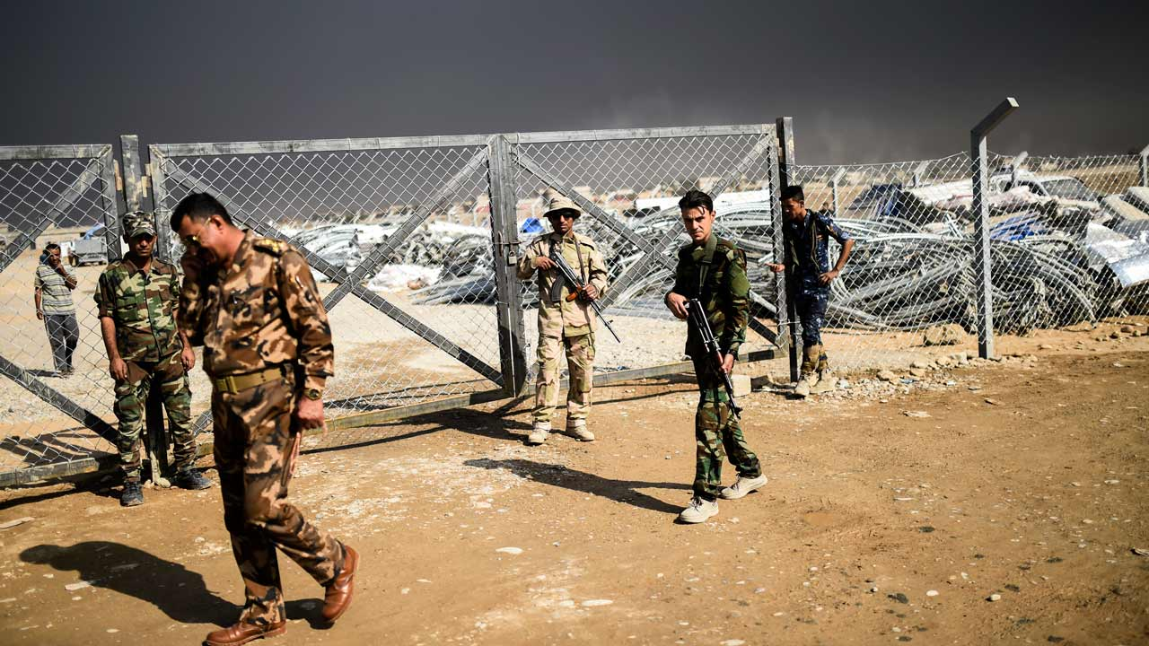 Iraqi army soldiers patrol outside a refugee camp in Qayyarah, south of Mosul, on October 29, 2016. Iraqi paramilitary forces launched an operation to cut the Islamic State group's supply lines between its Mosul bastion and neighbouring Syria, opening a new front in the nearly two-week-old offensive. BULENT KILIC / AFP