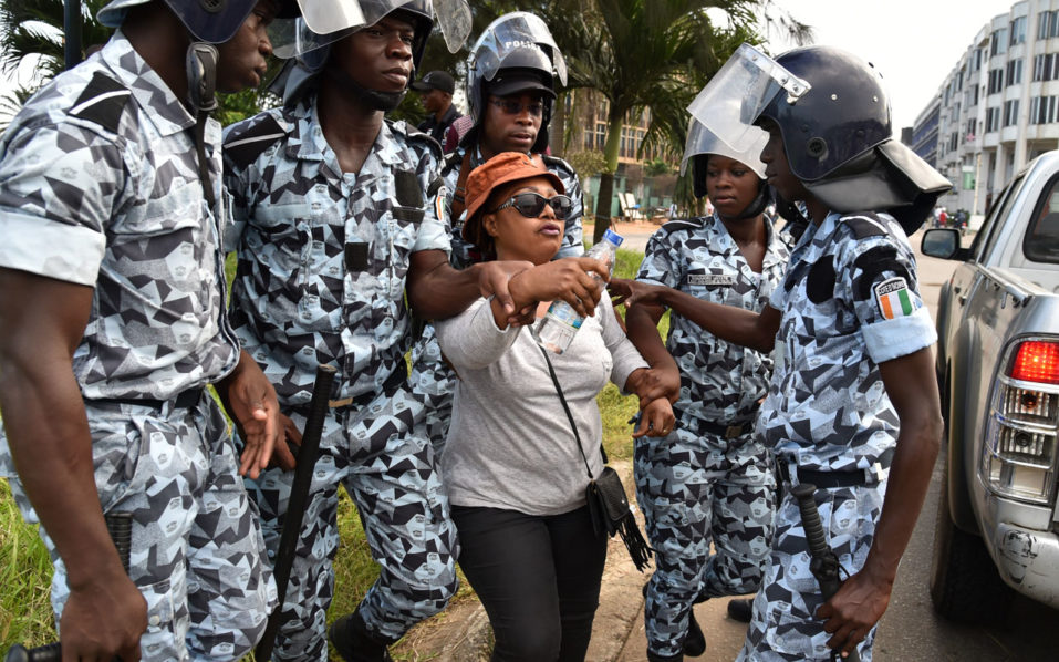 Ivory Coat's riot police arrest a woman during protests against a referendum on the adoption of a new constitution that changes contentious rules on presidential eligibility on October 20, 2016 in Abidjan. Ivory Coast police fired tear gas and arrested several political leaders on October 20 at a protest in the capital Abidjan against a proposed new constitution, according to an AFP journalist. The controversial constitution which changes contentious rules on presidential eligibility will be put to a referendum on October 29.  / AFP PHOTO / ISSOUF SANOGO