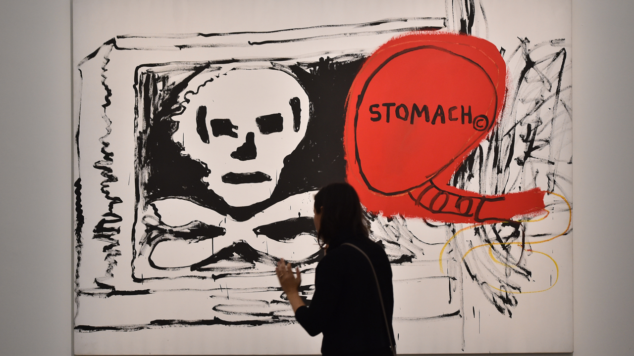 "A woman visits the exhibition ""Jean-Michel Basquiat"", a retrospective on Jean-Michel Basquiat's career from graffiti in New York to more complex work, on October 27, 2016 at the Mudec Museum in Milan. The show runs til February 26, 2017. / AFP PHOTO / GIUSEPPE CACACE / RESTRICTED TO EDITORIAL USE - MANDATORY MENTION OF THE ARTIST UPON PUBLICATION - TO ILLUSTRATE THE EVENT AS SPECIFIED IN THE CAPTION"