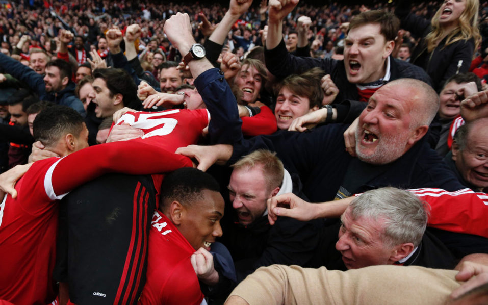 Manchester United's French striker Anthony Martial (C bottom) celebrates in the crowd after scoring their second goal during the English FA Cup semi-final football match between Everton and Manchester United at Wembley Stadium in London on April 23, 2016. / AFP PHOTO / ADRIAN DENNIS /
