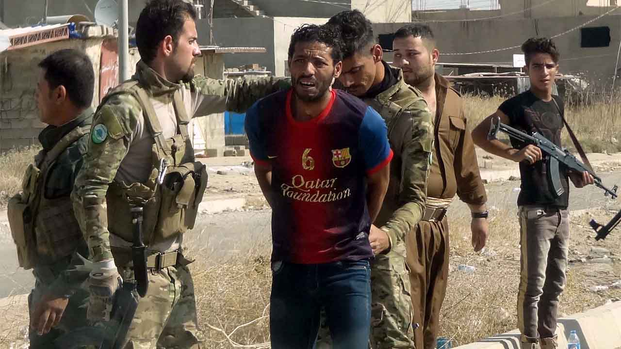Iraqi Kurdish security forces detain a suspected member of the Islamic State (IS) group as they patrol the eastern suburbs of Kirkuk on October 22, 2016, after jihadist gunmen attacked the city. Security forces battled for a second day with Islamic State gunmen who infiltrated Kirkuk in a brazen raid that rattled Iraq as it ramped up an offensive to retake Mosul. / AFP PHOTO / Marwan IBRAHIM