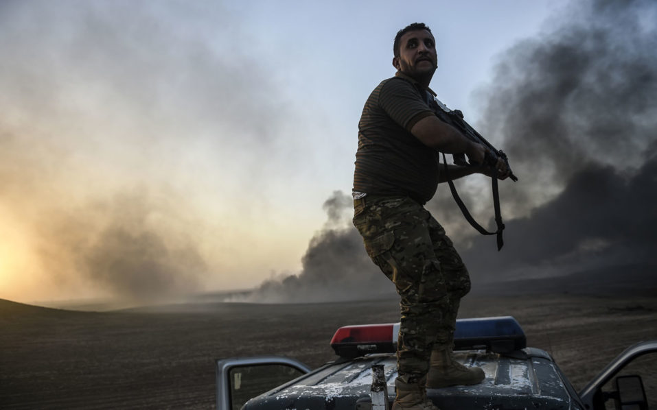 A member of the Iraqi government forces takes a position  on top of a vehicle as smoke rises on the outskirts of the Qayyarah area, some 60 kilometres (35 miles) south of Mosul, on October 20, 2016, during an operation against Islamic State (IS) group jihadists to retake the main hub city. In the biggest Iraqi military operation in years, forces have retaken dozens of villages, mostly south and east of Mosul, and are planning multiple assaults for October 20. / AFP PHOTO / BULENT KILIC