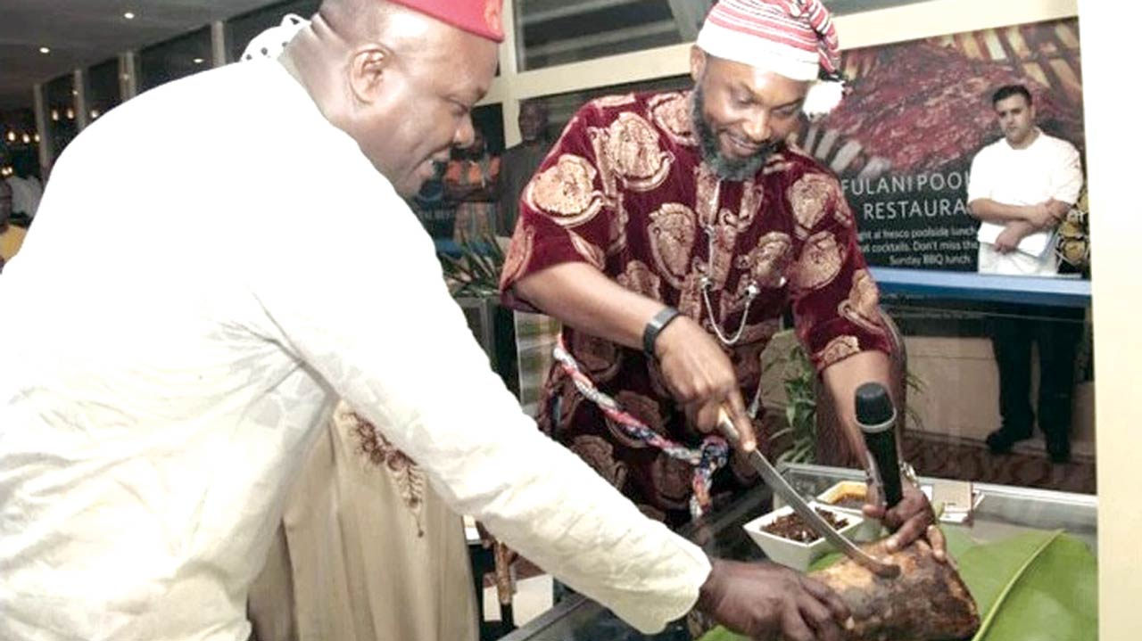 Former Minister of Aviation, Mr. Chidoka Osita (in red cap), performing the traditional cutting of the yam while the Chairman, Transcorp Hotels, Mr. Valentine Ozigbo helps out… in Abuja