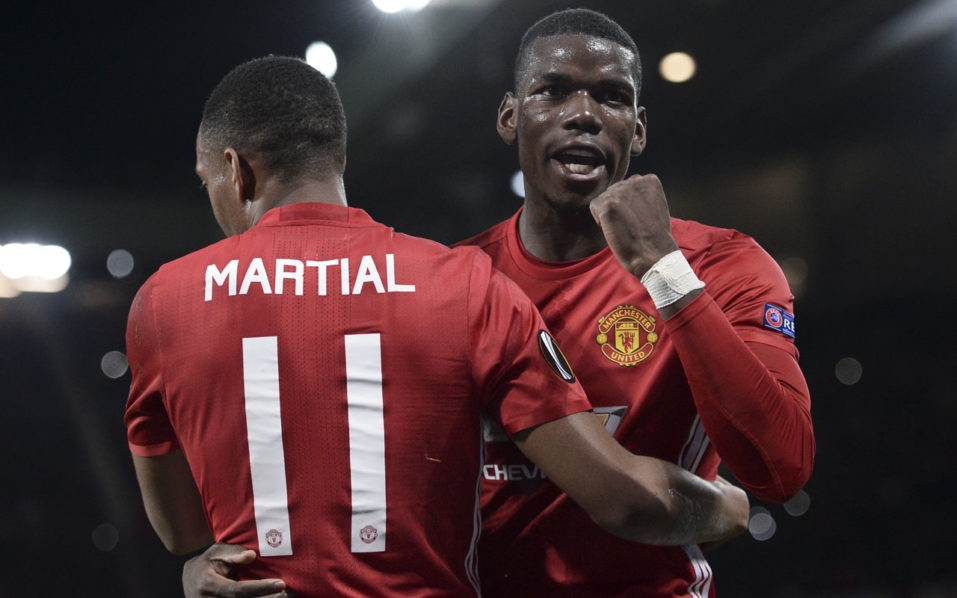 Manchester United's French striker Anthony Martial (L) embraces Manchester United's French midfielder Paul Pogba (R) as he celebrates scoring their second goal from the penalty spot during the UEFA Europa League group A football match between Manchester United and Fenerbahce at Old Trafford in Manchester, north west England, on October 20, 2016. / AFP PHOTO / OLI SCARFF