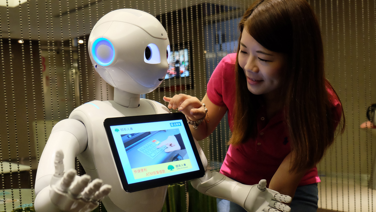 "A woman gives a comand to a robot named Pepper during a press conference organized by Cathay Financial Holdings in Taipei on October 6, 2016. A mini robot called ""Pepper"" started work alongside human colleagues at banks and an insurance company in Taiwan, enlisted with entertaining bored customers -- and giving them the hard sell. / AFP PHOTO / SAM YEH"