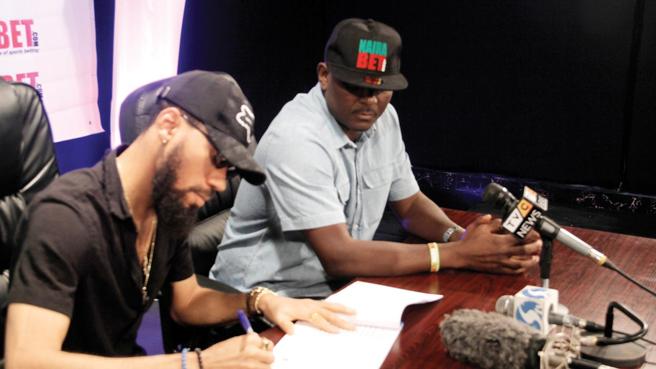Nairabet's Chairman, Akin Alabi (right), watches as Phyno signs the contract renewing his endorsement of the sports betting outfit for another year…on Tuesday.