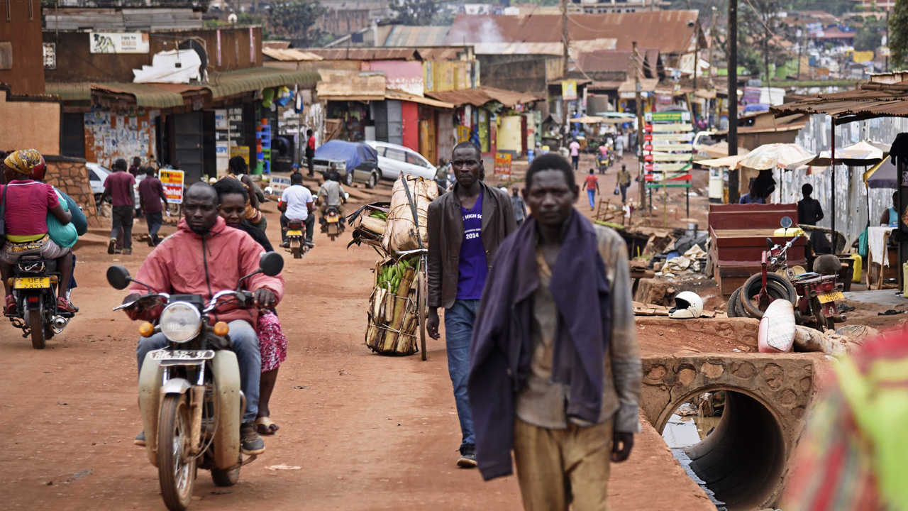 "Brian Mugabi (C), brother to Phiona Mutesi, walks along a street in Katwe, a Kampala suburb, on September 29, 2016. Standing on a drab side-street next to an open sewer in the Ugandan capital Kampala, Brian Mugabi points to the site of his former family home and reflects on how much the game of chess has changed their lives. The family's story is now the basis for the feel-good Disney movie ""Queen of Katwe"" which premiered in Uganda last weekend with Oscar-winning Kenyan actress Lupita Nyong'o playing the role of Phiona's mother. PHOTO: AFP/ ISAAC KASAMANI"